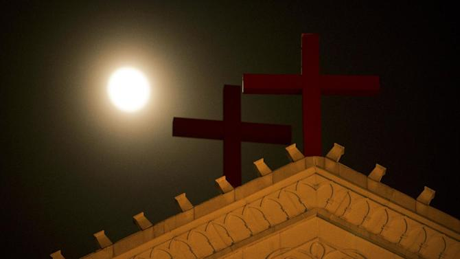 In this July 29, 2015 photo, the moon rises above a pair of crosses on the roof of Holy Trinity Church in Wenzhou in eastern China's Zhejiang Province, where church members are keeping a 24-hour vigil to watch for Chinese government workers coming to remove the building's crosses. A massive government campaign is underway in Zhejiang, where authorities are believed to be under a two-month deadline to remove crosses from the spires, vaults, roofs and wall arches of the 4,000 or so Protestant and Catholic churches that dot the landscape of the region. (AP Photo/Mark Schiefelbein)