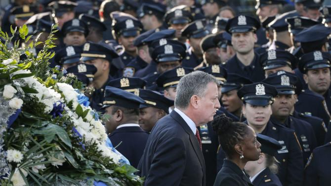 New York Mayor de Blasio and wife Chirlane walk past a sea of policemen while arriving for the funeral services of NYPD officer Ramos in the Queens borough of New York