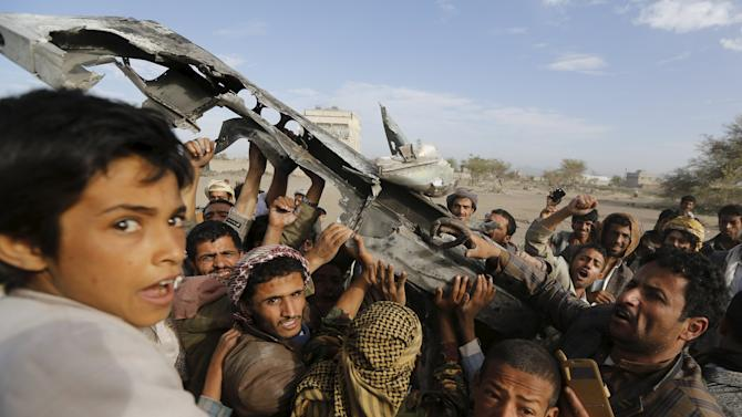 People react as they hold part of a Saudi fighter jet found in Bani Harith district north of Yemen's capital Sanaa