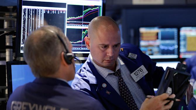 Trader Timothy Nick, left, and specialist Mario Picone confer on the floor of the New York Stock Exchange Wednesday, Oct. 22, 2014. Stocks are opening mixed as investors look over earnings reports from U.S. companies. (AP Photo/Richard Drew)
