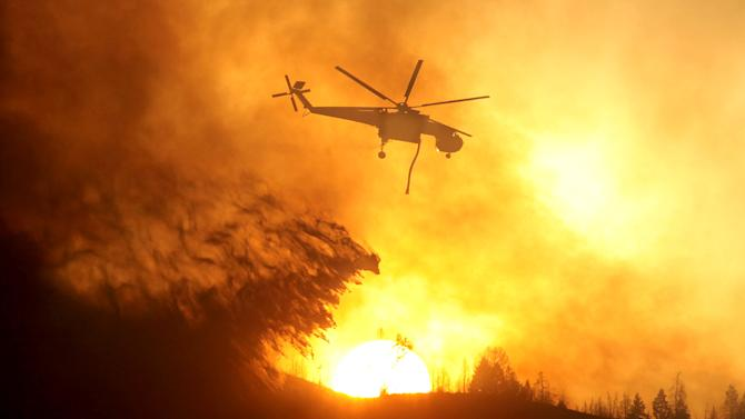 A helicopter makes a drop while battling the Beaver Creek Fire on Saturday, Aug. 17, 2013 north of Hailey, Idaho.(AP Photo/Times-News, Ashley Smith) Mandatory Credit