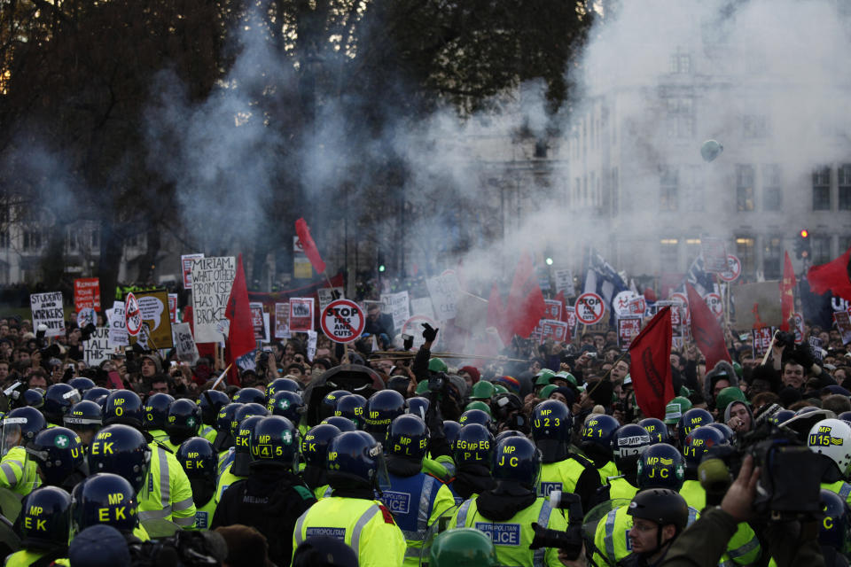 Protesters and police officers clash during a protest against an increase in tuition fees on the edge of Parliament Square in London, Thursday, Dec. 9, 2010.  Police clashed with protesters marching to London's Parliament Square as lawmakers debated a controversial plan to triple university tuition fees in England.(AP Photo/Karel Prinsloo)