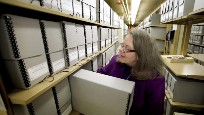 Archivist Voloise Armstrong, places a box of recently discovered documents in the stacks at the Eisenhower Presidential Library in Abilene, Kan. Friday, Dec. 10, 2010. The documents containing drafts of Eisenhower's farewell address and other correspondence were found in a Minnesota cabin belonging to Eisenhower's speechwriter. (AP Photo/Charlie Riedel)