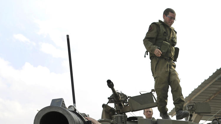 An ultra-Orthodox Jew of the Bratslav Hasidic sect, part of a team that gathered to show support for Israeli forces, jumps from a tank in southern Israel, close to the Israel Gaza Strip Border, Thursday, Nov. 22, 2012. A cease-fire agreement between Israel and the Gaza Strip's Hamas rulers took effect Wednesday night, bringing an end to eight days of the fiercest fighting in years and possibly signaling a new era of relations between the bitter enemies. (AP Photo/Tsafrir Abayov)