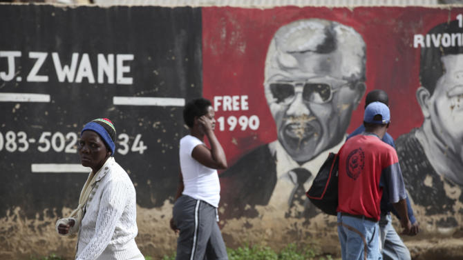 People walk past a mural showing former South African President Nelson Mandela in the Soweto area of Johannesburg, South Africa, Sunday, Dec. 9, 2012. South Africa's presidency says that Mandela, 94, was admitted to a hospital Saturday in the nation's capital for tests. (AP Photos/Jon Gambrell)