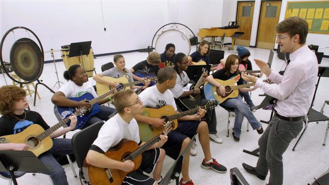 ADVANCE FOR USE SATURDAY, JUNE 16 AND THEREAFTER - In this May 11, 2012 photo, Springfield Southeast High School students are seen in the Introduction to Guitar class in Springfield, Ill. Days after President Barack Obama called on the states to keep students in schools and raise the dropout age to 18, Illinois Gov. Pat Quinn proposed that Illinois should do so. Not everyone met the proposal with Quinn's enthusiasm, saying the state should consider it carefully before pushing up the age. (AP Photo/Seth Perlman))