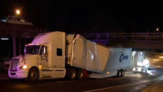 Truck stuck under bridge blocks roadway