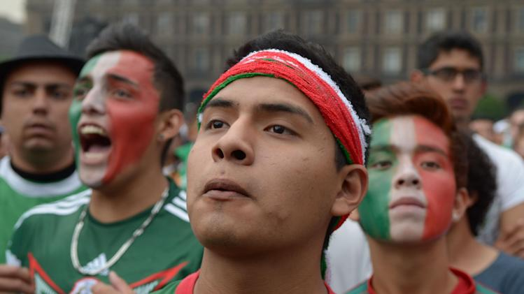 Mexico soccer fans watch their team's 2014 World Cup match with Croatia on giant television screens in Mexico City's main square, the Zocalo, Monday, June 23, 2014. Needing only a tie to advance to the second round of the World Cup for a sixth straight time, Mexico is bound to please its fans