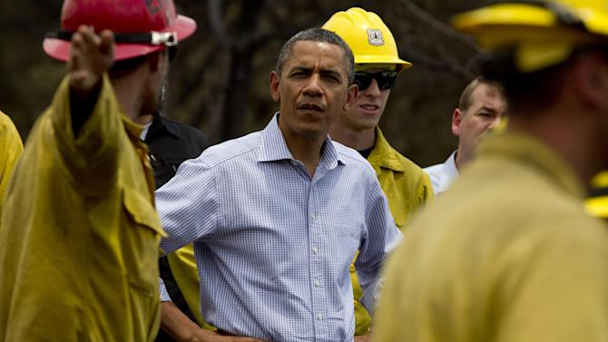"President Barack Obama talks with firefighters as he tours the Mountain Shadow neighborhood devastated by a wildfire, Friday, June 29, 2012, in, Colorado Springs, Colo. After declaring a ""major disaster"" in the state early Friday and promising federal aid, President Obama got a firsthand view of the wildfires and their toll on residential communities. More than 30,000 people have been evacuated in what is now the most destructive wildfire in state history. (AP Photo/Carolyn Kaster)"