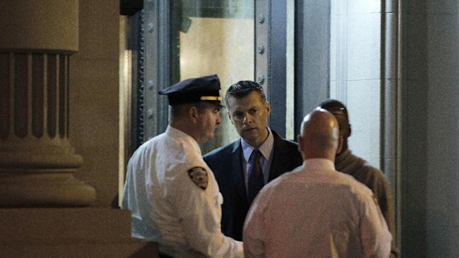 Police confer in front of the luxury Manhattan apartment building where police say a nanny stabbed two small children to death in a bathtub and then stabbed herself in New York, Thursday, Oct. 25, 2012. Police say the children's mother found the scene after returning home with another child. (AP Photo/Kathy Willens)