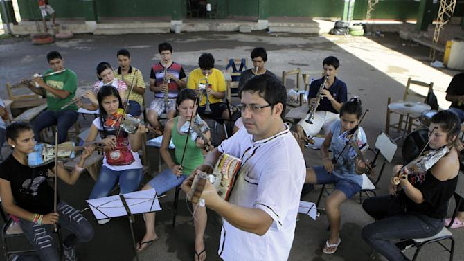 """In this Dec. 11, 2012 photo, Music Director Fabio Chavez leads his students from """"The Orchestra of Instruments Recycled From Cateura"""" in a practice session in Cateura, a vast landfill outside Paraguay's capital of Asuncion, Paraguay.  Chavez had learned clarinet and guitar as a child, and had started a small music school in another town in Paraguay before he got a job with an environmental organization teaching trash-pickers in Cateura how to protect themselves. Chavez opened a tiny music school at the landfill hoping to keep youngsters out of trouble. But he had just five instruments to share. (AP Photo/Jorge Saenz)"""