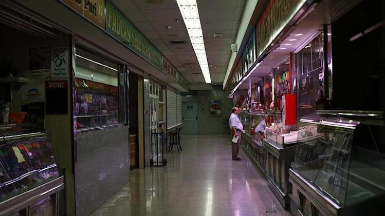 A man shops at a butcher's store in a local market in Madrid