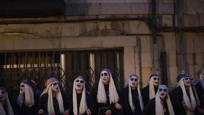 Townswomen dressed as Lamia, with their faces painted white and eyes darkened, sing and dance in the Basque coastal town of Mundaka