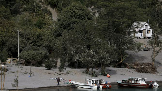 A man walks along a shore of Petrohue lake covered with ashes from Calbuco Volcano, in the vicinity of Puerto Montt city