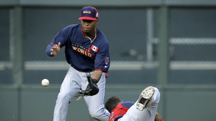 World's Dalton Pompey, left, and Gabby Guerrero, right, look to field a single hit by United States' J.P. Crawford during the sixth inning of the All-Star Futures baseball game Sunday, July 13, 2014, in Minneapolis. (AP Photo/Jeff Roberson)