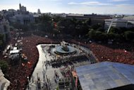 People wait to watch the Spanish national football team parade in Madrid, a day after it won the final match of the Euro 2012 championships 4-0 against Italy in Kiev