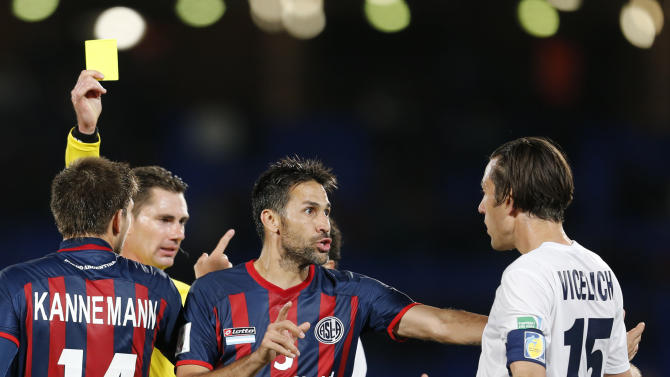 San Lorenzo's Mario Yepes, center, argues with Auckland City FC's Ivan Vicelich after Auckland City FC's Cameron Lindsay received a yellow card during the semi final soccer match between Auckland City FC and San Lorenzo at the Club World Cup soccer tournament in Marrakech, Morocco, Wednesday, Dec. 17, 2014. (AP Photo/Abdeljalil Bounhar)