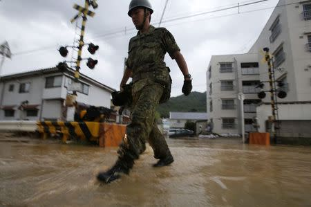 JSDF soldier walks on a flooded street in the rain at a site where a landslide swept through a residential area at Asaminami ward in Hiroshima