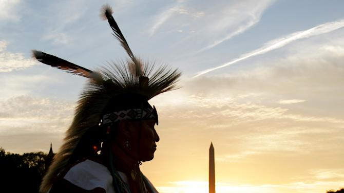 FILE - In this Tuesday, Sept. 21, 2004 photo, a member of the Northern Arapaho Tribe who lives on the Wind River Indian Reservation in Wyoming, attends the festivities on the National Mall for the opening of the National Museum of the American Indian in Washington. The Washington Monument is in the background. Federal agencies questioned how the Northern Arapaho government spent at least $3.4 million since 2007, but decided not to recover any of the money - and even increased funding. The Wyoming tribe is hardly unique. An Associated Press review of summaries of audits performed by private firms showed that auditors consistently raised serious concerns about 124 of 551 tribal governments, schools or housing authorities that received at least 10 years of substantial federal funds since 1997. (AP Photo/Susan Walsh, File)