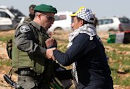 A Palestinian activist is arrested by an Israeli soldier in the Yatta, south of the West Bank city of Hebron on February 9, 2013. Israel's army has forced Palestinian activists to evacuate a West Bank encampment they tried to set up to protest against settlement building, witnesses said