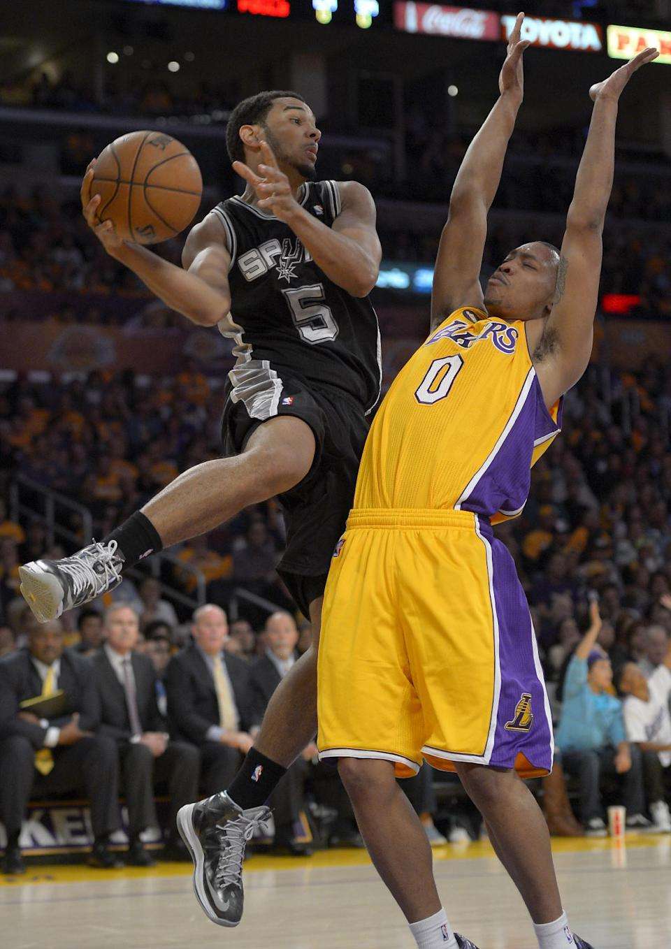San Antonio Spurs guard Cory Joseph, left, passes around Los Angeles Lakers guard Andrew Goudelock during the first half in Game 3 of a first-round NBA basketball playoff series, Friday, April 26, 2013, in Los Angeles. (AP Photo/Mark J. Terrill)