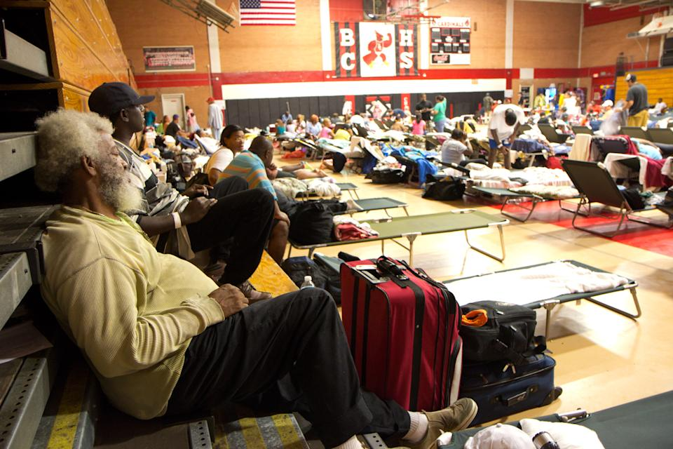 Norward Tinson, left, rests at a shelter at Belle Chasse, La., High School for residents of Plaquemines Parish, a rural area outside New Orleans, that was hit hard by Hurricane Isaac on Wednesday, Aug. 29, 2012. (AP Photo/Erik Schelzig)