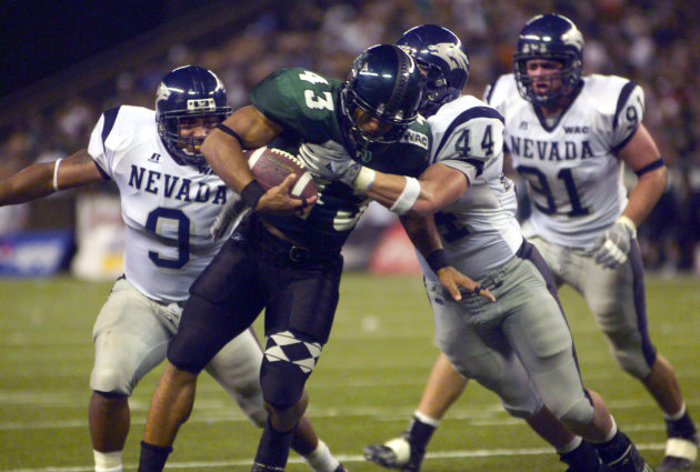 FILE - In this Oct. 9, 2004, file photo, Hawaii's Bryan Maneafaiga (43) scores a touchdown against Nevada in Honolulu. With uneven testing for steroids and inconsistent punishment, college football pl