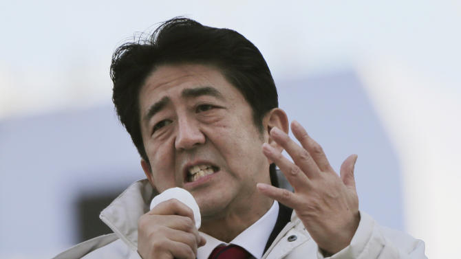 In this Tuesday, Dec. 11, 2012 photo, Japan's main opposition Liberal Democratic Party (LDP) President Shinzo Abe speaks during a campaign rally for the Dec. 16 parliamentary elections in Machida, on the outskirts of Tokyo. Former Prime Minister Abe, who is poised to head the government again if his LDP does as well most polls are forecasting, favors forcing the central bank to do whatever it takes to meet an inflation target, of perhaps 2 percent, to break the economy out of its deflationary funk. The party slogan on his jacket read: We get back Japan. (AP Photo/Itsuo Inouye)