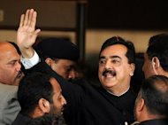 Pakistan's Prime Minister Yousuf Raza Gilani (C) is escorted by security as he arrives at the Supreme Court building in Islamabad April 26. Gilani on Friday refused to step down after his contempt of court conviction, saying only the country's parliament could remove him from office