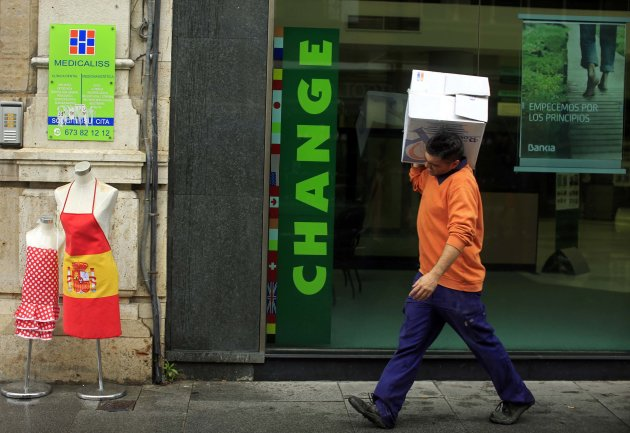 A worker carries a box as he walks past a branch of Spanish lender Bankia in the Andalusian capital of Seville