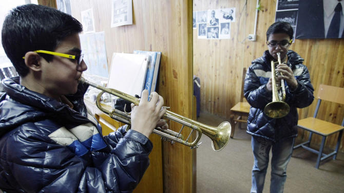 In this Monday,  Jan. 7, 2013 photo, Ahmad Baset of Afghanistan  practices playing the trumpet in front of a mirror in a class at the Afghanistan National Institute of Music in Kabul, Afghanistan. Dozens of Afghan teenagers including former street kids or orphans aged 10 to 22, will be playing in the Afghan Youth Orchestra which begins a 12-day U.S. tour on Feb. 3 and includes concerts at Washington's Kennedy Center - President Barrack Obama has been invited - New York's Carnegie Hall and the New England Conservatory in Boston. (AP Photo/Musadeq Sadeq)