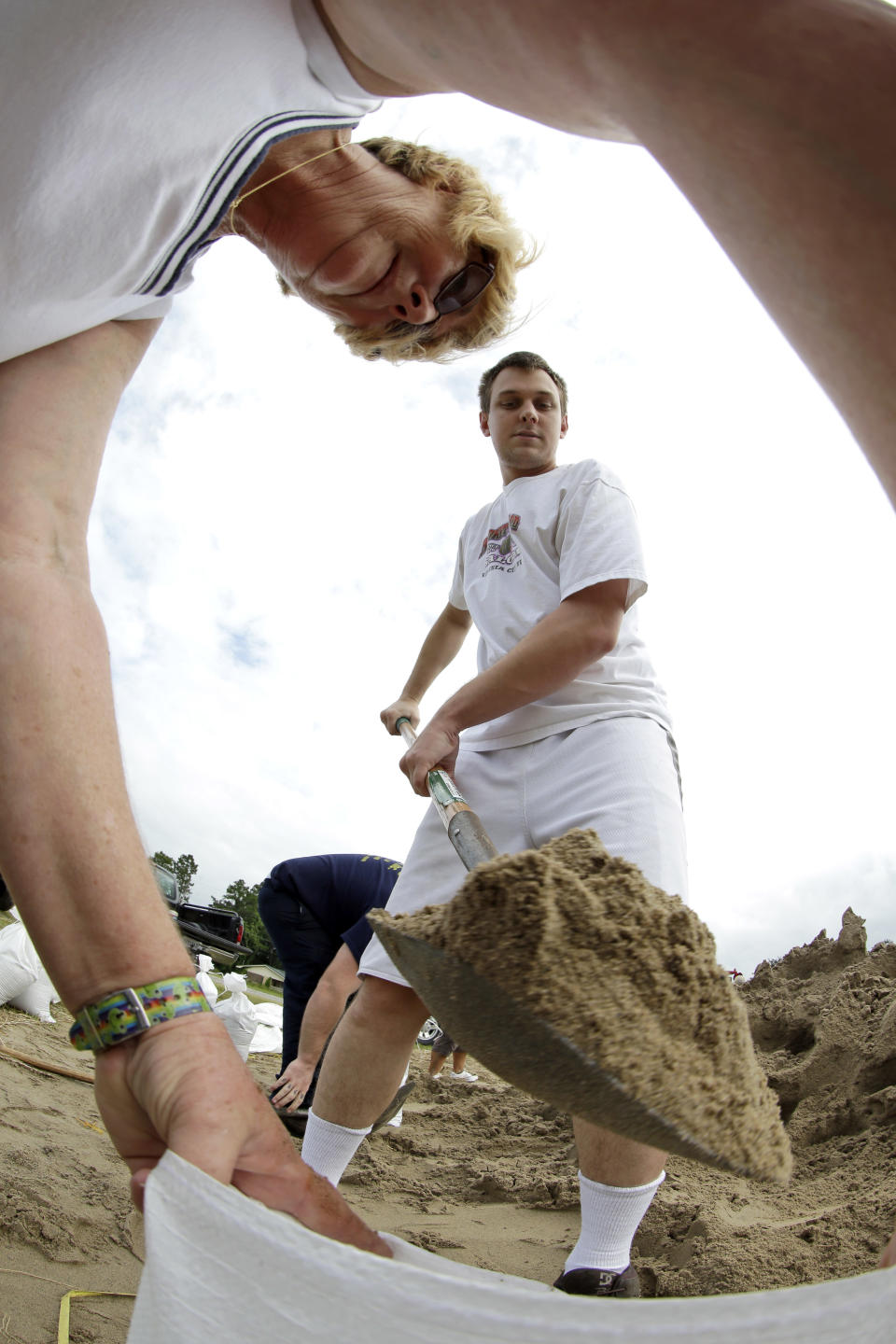 Richard Sackfield, center, fills a sandbag for Annie Savoie, left, as Isaac nears landfall Tuesday, Aug. 28, 2012, in Houma, La. Isaac is churning it's way across the Gulf of Mexico heading towards Louisiana. (AP Photo/David J. Phillip)