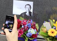 A man uses his iPhone to photograph flowers and a photocopy image of Steve Jobs that is placed at the entrance at the Apple Store in Sydney, Thursday, Oct. 6, 2011. Steve Jobs, the Apple founder and former CEO who invented and masterfully marketed ever-sleeker gadgets that transformed everyday technology, from the personal computer to the iPod and iPhone, died Wednesday. (AP Photo/Rick Rycroft)