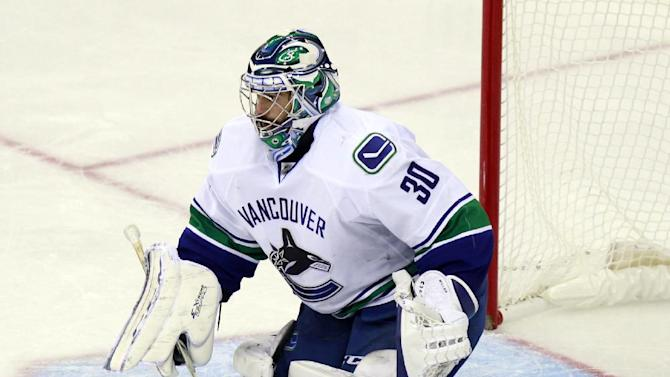 Vancouver Canucks goalie Ryan Miller makes a stop against the Columbus Blue Jackets during the third period of an NHL hockey game in Columbus, Ohio, Friday, Nov. 28, 2014. Vancouver won 5-0. (AP Photo/Paul Vernon)