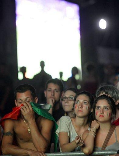 Italian supporters react in front of a giant screen
