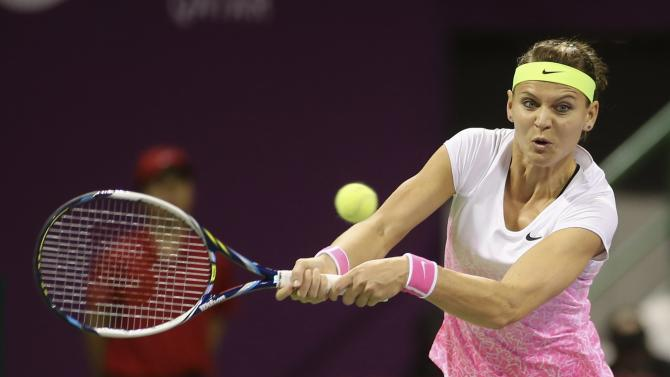 Safarova returns the ball to Azarenka during their women's singles final match at the Qatar Open tennis tournament in Doha