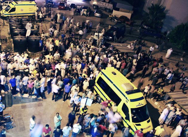 In this Sunday, Aug. 5, 2012 photo, Egyptians stand outside the El Arish hospital, after an attack which Egypt and Israel blamed on Islamist militants from the Hamas-run Gaza Strip in Egypt's northern Sinai Peninsula. Israeli intelligence services had reports of an impending attack from Egypt's Sinai Peninsula and therefore were able to thwart the latest assault by suspected Islamist militants who killed scores of Egyptian soldiers at a border checkpoint, then stole two of their vehicles to burst through a security fence into Israel, Israel's chief military spokesman said Monday, Aug. 6, 2012. (AP Photo)