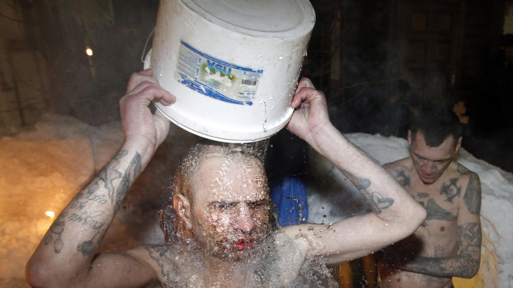 "FILE - In this file photo dated Thursday, Jan. 19, 2012, inmates of a prison colony pour cold water over themselves to celebrate Epiphany at St. Peter and Paul Cathedral in the Murmansk region of northern Russia.  The contract-style killing of Russian mobster Aslan Usoyan, also known as Grandpa Khasan, on Wednesday Jan16, 2013, drew renewed attention to the extensive and elaborate culture of the country's underworld figures who call themselves ""crowned thieves"" and ""thieves in law.""  Only top criminals are allowed to have tattoos which signal their privileged status within the criminal underworld, and may contain obscure codes, such as MIR (peace) meaning ""Only capital punishment will correct me, and the Nazi swastika means rejection of everything Soviet (but does not make its bearer a neo-Nazi). (AP Photo/ Andrey Pronin, FILE)"
