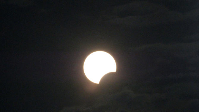 A partial solar eclipse is seen at Sanur beach, Bali, Indonesia, Friday, May 10, 2013. (AP Photo)