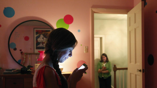 In this Thursday, May 24, 2012 photo, Anna Schiferl, foreground, texts her mother, Joanna, as they pose for a photograph in their LaGrange, Ill. home. Statistics from the Pew Internet & American Life Project show that, these days, many people with cell phones prefer texting over a phone call. It's not always young people, though the data indicates that the younger you are, the more likely you are to prefer texting. But many experts say the most successful communicators will, of course, have the ability to do both talk or text, and know the most appropriate times to use those skills. (AP Photo/Charles Rex Arbogast)
