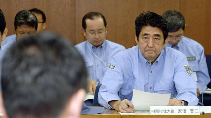 Japan's Prime Minister Shinzo Abe, right, is briefed at Hiroshima Prefectural Government in Hiroshima, western Japan Monday, Aug. 25, 2014. Abe is visiting Hiroshima to see search and cleanup operations following landslides around the city that killed at least 50 people. (AP Photo/Kyodo News) JAPAN OUT, MANDATORY CREDIT