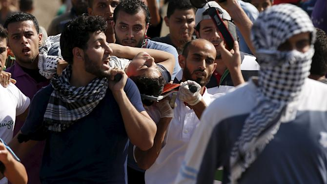 Palestinians carry a wounded protester, who was shot by Israeli troops, during clashes near the Israeli border fence in northeast Gaza