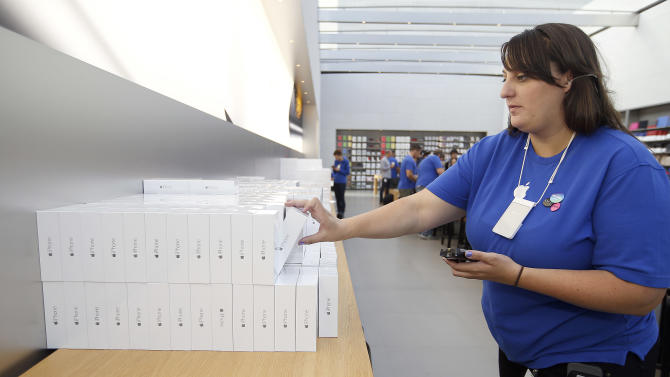 FILE - In this Sept. 19, 2014 file photo, an Apple employee grabs an iPhone 6 for a customer at the Apple Store during the launch and sale of the new iPhone 6 and 6 Plus smartphones, in Palo Alto, Calif. Apple on Monday, Oct. 20, 2014 said it sold 39.3 million iPhones in the last quarter, or 16 percent more than a year ago, which is a record for the quarter. That's partly due to excitement over new iPhone 6 and 6 Plus models that Apple began selling last month. (AP Photo/Tony Avelar, File)
