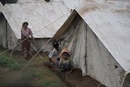 <p>Myanmar Muslim Rohingya people dig ditches outside tents at a temporary relief camp for people displaced by days of sectarian violence on the outskirts of Sittwe on June 15. The nation's authorities have faced heavy criticism from rights groups after deadly unrest between Muslim Rohingya and ethnic Rakhine Buddhists in western Rakhine state.</p>