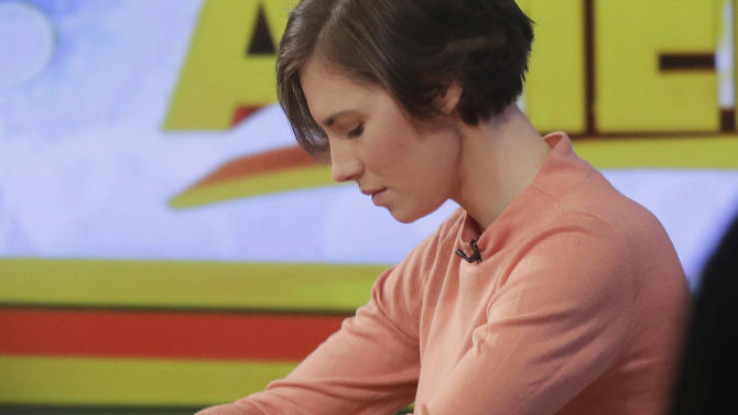 """Amanda Knox bows her head during a television interview, Friday, Jan. 31, 2014 in New York. Knox said she will fight the reinstated guilty verdict against her and an ex-boyfriend in the 2007 slaying of a British roommate in Italy and vowed to """"never go willingly"""" to face her fate in that country's judicial system . """"I'm going to fight this to the very end,"""" she said in an interview with Robin Roberts on ABC's """"Good Morning America."""" (AP Photo/Mark Lennihan)"""