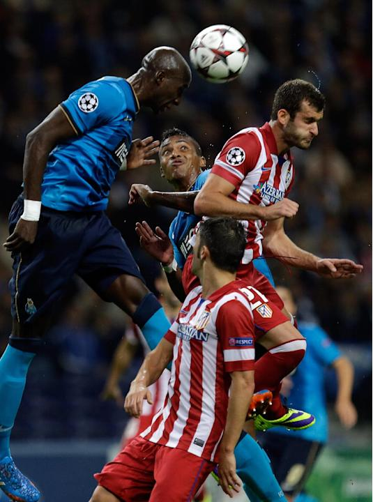 Porto's Alex Sandro, center, watches his teammate Eliaquim Mangala, left, head the ball during the Champions League group G soccer match between FC Porto and Atletico de Madrid Tuesday, Oct. 1, 2013,