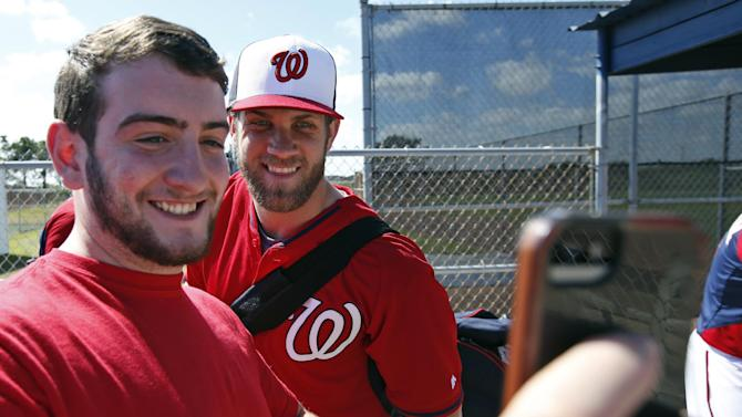 Anthony Cosenza, from Staten Island, N.Y., takes a selfie with Washington Nationals left fielder Bryce Harper after a spring training baseball workout, Thursday, Feb. 20, 2014, in VIera, Fla