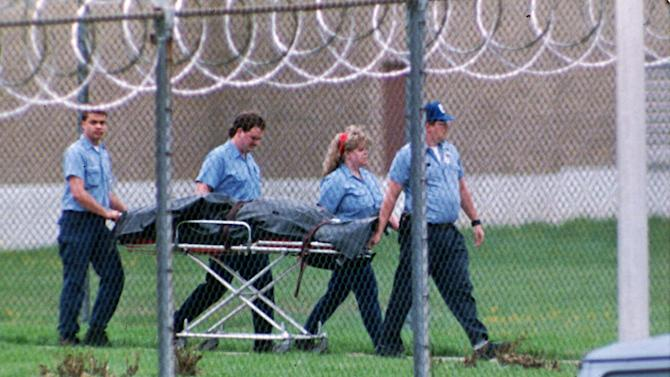 FILE - This April 15, 1993 file photo shows the body of Southern Ohio Correctional Facility guard Robert Vallandingham carried from the prison in Lucasville, Ohio, after his body was found in the prison yard. In the 20 years since the nation's longest deadly prison riot broke out in Lucasville, no interviews have been granted with the five men sentenced to death in the killing of a guard. Yet time has brought new evidence and insights that will dominate events marking the 20th anniversary of the 11-day siege of April 1993. (AP Photo/Mark Duncan, File)