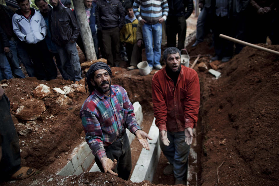 Cemetery workers prepare graves for a  three Free Syrian Army fighters in Idlib, north Syria, Saturday, March 3, 2012. (AP Photo/Rodrigo Abd)