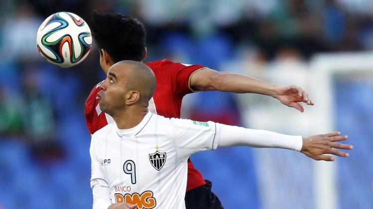 Diego Tardelli of Brazil's Atletico Mineiro fights for the ball with Dario Conca of China's Guangzhou Evergrande during their 2013 FIFA Club World Cup third place soccer match in Marrakech stadium